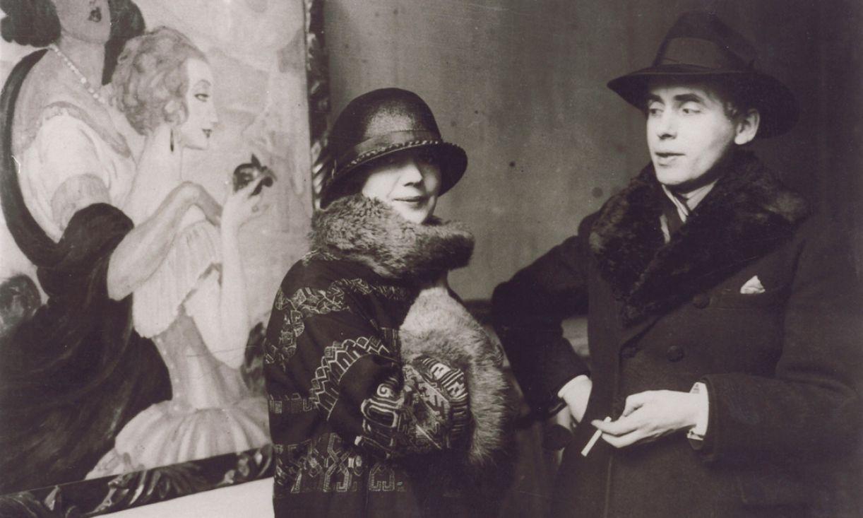Casal Gerda e Einar Wegener posa em frente à pintura dela