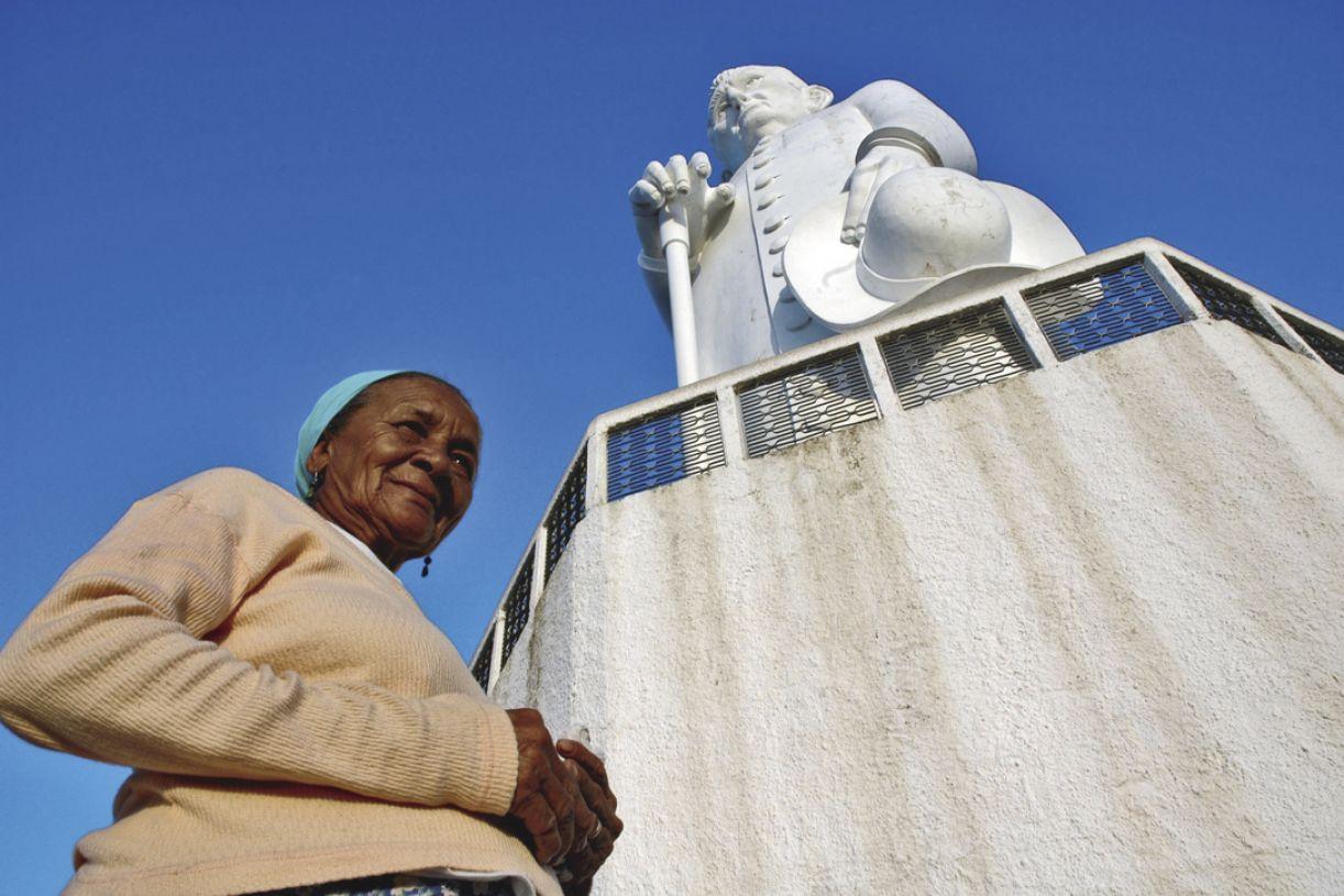 Romeiros fazem pose diante da estátuade concreto de 27 metros de altura do religioso