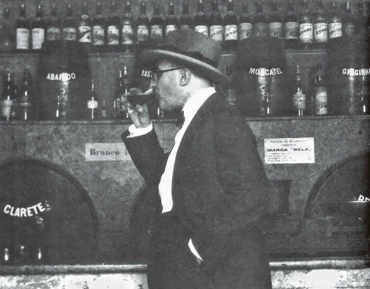Em flagrante: Fernando Pessoa bebendo vinho na firma Pereira da Fonseca à frente e um barril de clarete