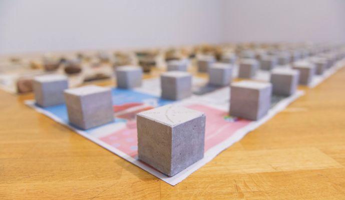 Na obra 'Primeira pedra', o artista propõe que o visitante saia da exposição em busca de uma pedra para trocar por um dos cubos de concreto utilizados por ele. Imagem: Levi Fanan/Divulgação