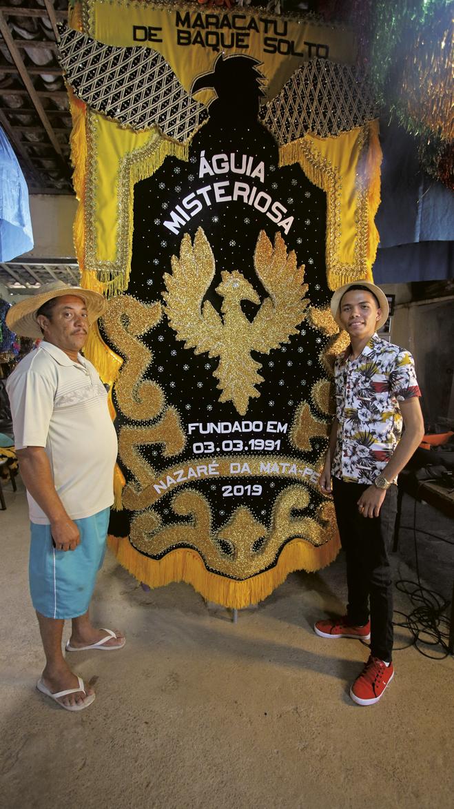 Seu Vicente, presidente do Águia Misteriosa, e Anderson, diante de um estandarte da agremiação
