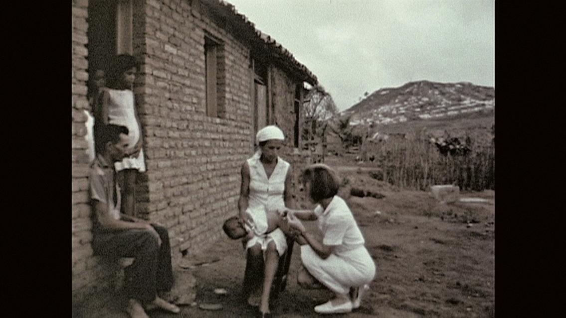 Voluntária dos Corpos da Paz, ajoelhada, vacina bebê no colo de mulher sentada. Pessoas à esquerda observam a cena da porta de uma casa.