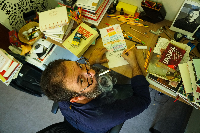 Escritor Antonio Martinelli, com cigarro na boca, olha para cima e diretamente para a câmera em mesa de trabalho com livros